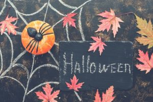 Halloween, pumpkin, spider, red maple leaves, spider web drawn in chalk on a dark rustic background. Signboard with with text-Halloween.